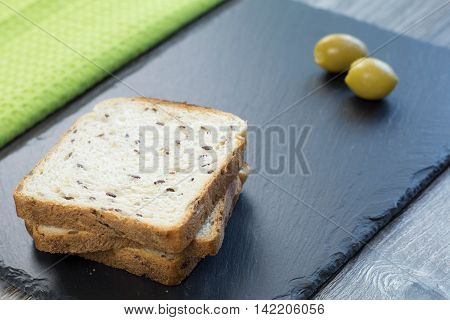 Fresh whole grain toast with linseed and two green olives on a black stone tray and green cloth in the background.