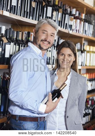 Smiling Couple With Wine Bottle In Shop