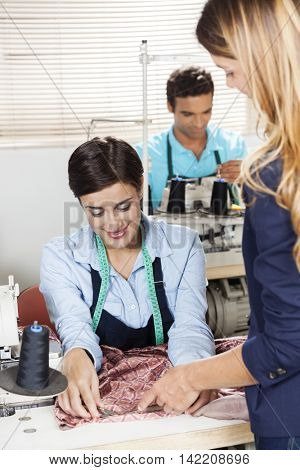 Tailor Explaining Employee At Workbench
