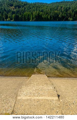 Beautiful Lake Cowichan in Canada. Stone stairs leading to the lake water.