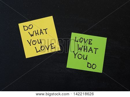 Yellow and green note paper on black wooden background. 'Love What You Do and Do What You Love' notes pasted on blackboard.