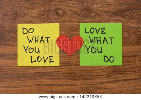 Yellow and green note paper with red heart on rustic wooden background. 'Love What You Do and Do What You Love' notes pasted on blackboard.