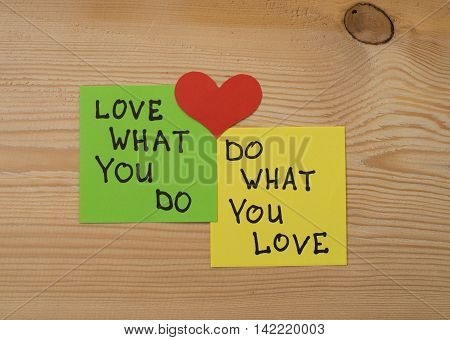 Yellow and green note paper with red heart on rustic wooden background. 'Love What You Do and Do What You Love' notes . I love my job concept