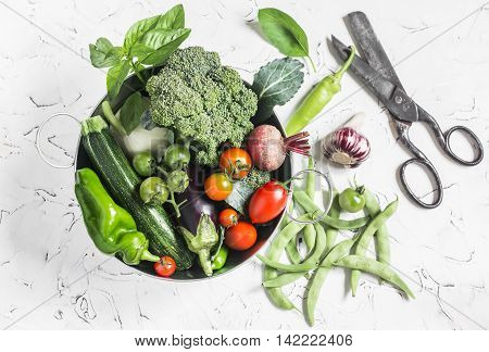 Fresh vegetables - broccoli zucchini beets peppers tomatoes green beans garlic basil in a metal basket on a light background. Healthy food