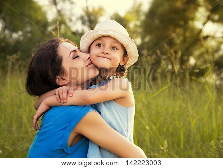 Beautiful Happy Mother Hugging And Kissing Her Grimacing Fun Daughter On Summer Bright Background