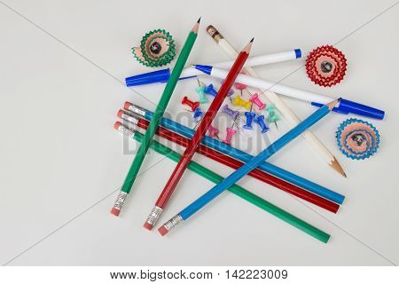 Pens, pencils, push pins, and flower pencil shavings on white background