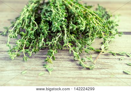 Sprigs of thyme on an old wooden background selective focus