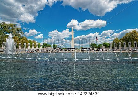Tourists and other people are seen in the picture near the fountain in the National World War II memorial and the Washington monument in the background.