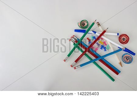 Pens, pencils, push pins, and flower shaped pencil shavings on white background on right