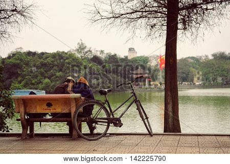Hanoi, Vietnam - 10 March, 2012: The couple sit on the bench beside their bicycle at Hoan Kiem lake