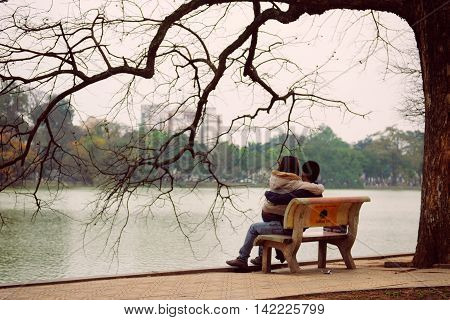 Hanoi, Vietnam - 10 March, 2012: The couple sit on the bench at Hoan Kiem lake
