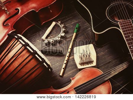 Set of musical instruments on dark wooden background: guitar, violin, harmonica, cello and others. Top view. Vintage retro effect filtered, hipster style