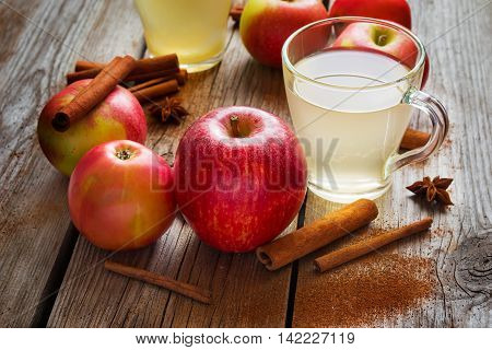 Apples cider and cinnamon on old wooden table.