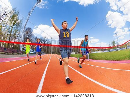 Portrait of teenage sprinter, race champion, crossing finish line on the stadium