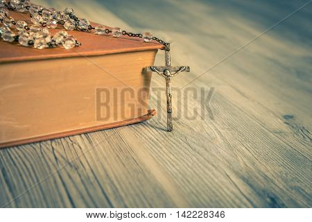 vintage rosary beads on old booksclose up.