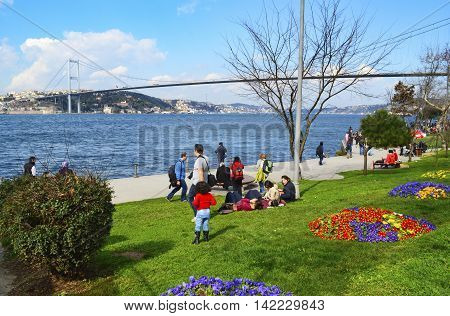 Istanbul Turkey - March 10 2013: Spring season people Istanbul Strait on the beach enjoying the spring. View of the European side of Istanbul from the Bosphorus. The Bosphorus Bridge (Turkish: Bogazici Koprusu)