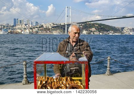 Istanbul Turkey - March 10 2013: Turkish vendor sells bagels a type of Turkish bread in the coast of Istanbul on the Bosphorus. In the background