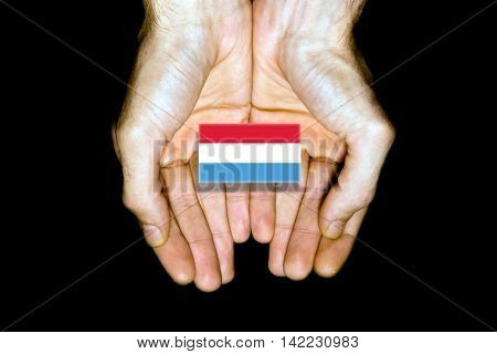 Flag Of Luxembourg In Hands On Black Background