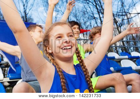 Close-up picture of smiling teenage girl, sports fan celebrating the win at the tribune