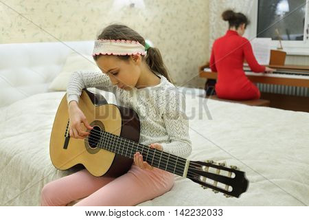 two in bedroom: daughter plays guitar and mother playing on synthesizer in background