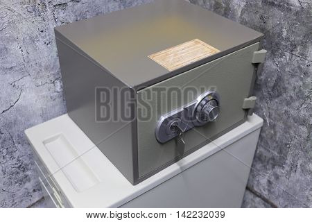 small metal safe with key and combination lock on box in corner of room