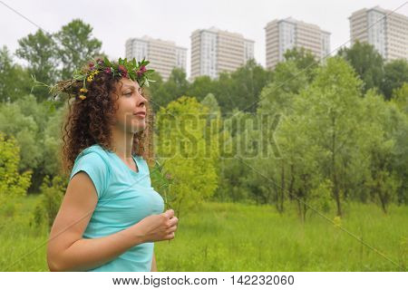 half length portrait of young woman with wreath of flowers urban wooded area near apartment complex, holding clover photo in profile