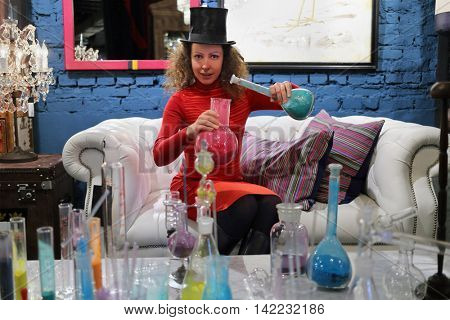 woman in hat sitting on couch and holding flasks with colored powder
