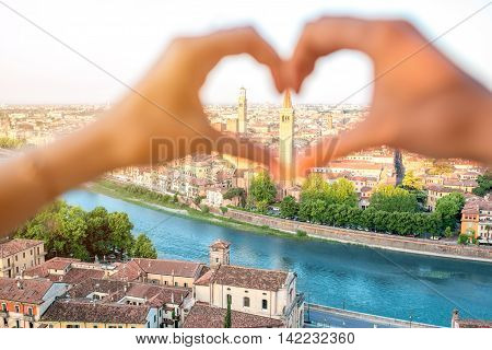 Female hands making heart shape on Verona cityscape background. Verona is famous city of love in the north of Italy.