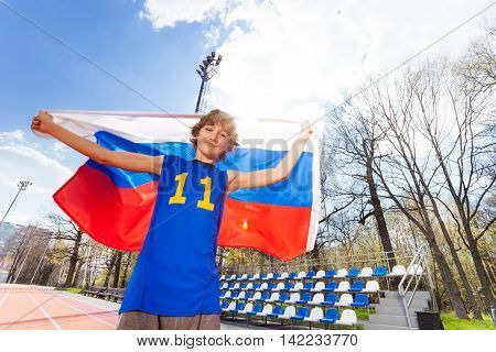 Happy teenage boy in sportswear waving Russian flag in the stadium on sunny day