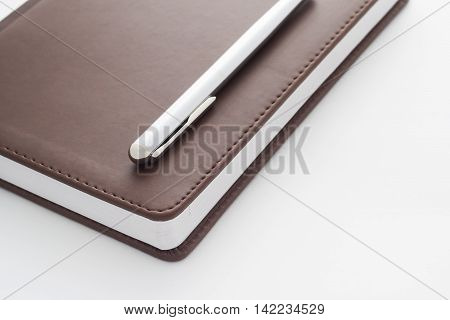 Metal Handle Lying On A Leather-bound Brown Diary Which Belongs To Businessman.