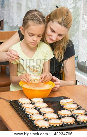 Mother Helps Daughter To Pour Batter Into The Mold For Cupcakes