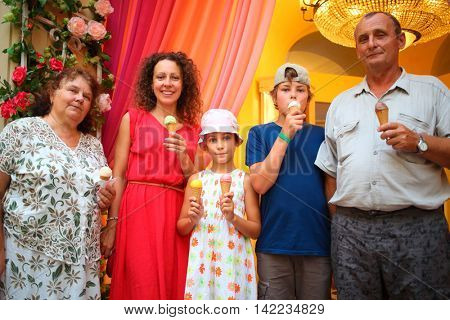 happy family with ice cream posing in front of camera in shopping center