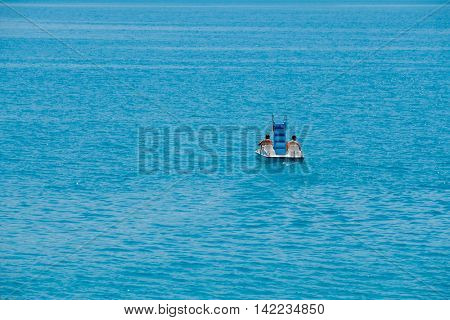 Couple riding pedal boat on a lake