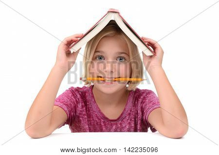 young girl with a book on her head and pencil in mouth