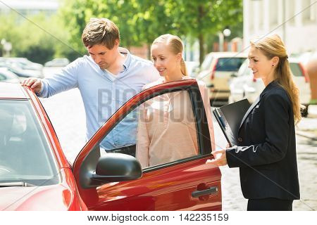 Saleswoman Standing Besides Couple Looking At New Red Car