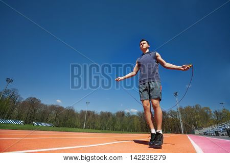 Active teenage athlete skipping the rope outside on the stadium, bottom view