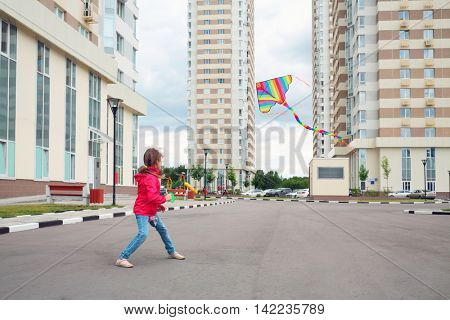 Girl in red jacket and blue jeans let kite on local area of high-rise buildings