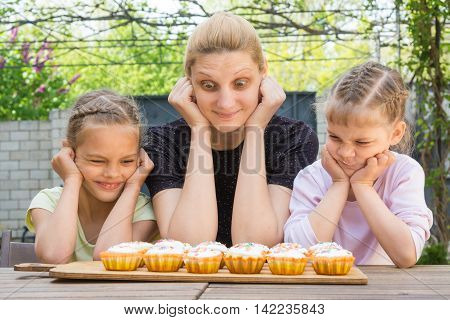 Mother And Two Daughters With Different Funny Emotion Looking At Easter Cupcakes