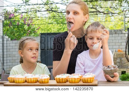 Mother And Two Daughters Lick Spoons With Confectionery Icing For Easter Cupcakes