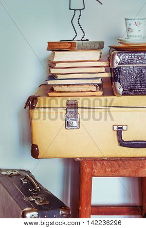 Vintage Composition with old books suitcases and stool. Toning.