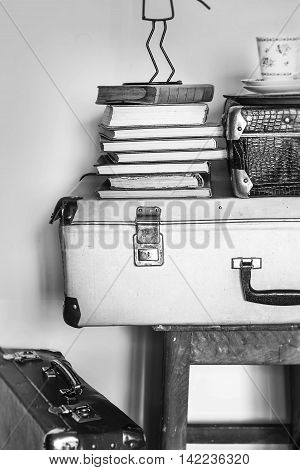 Vintage composition of old suitcases stools and books. Black an white