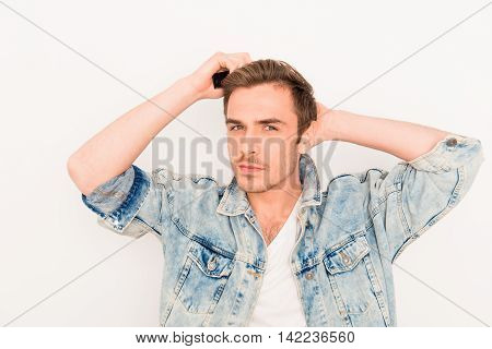 Portrait Of Young Guy In Jeans Jacket Combing Hair