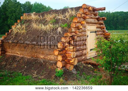 hut with dirt roof is collected from logs in forest on field