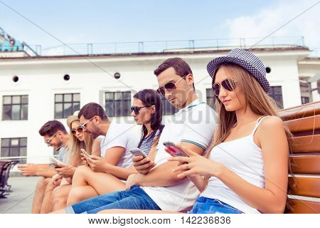 Successful Young  Boyfriends And Girlfriends In Glases  Using Their Smartphone At Summertime