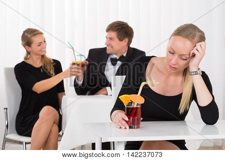 Depressed Woman Sitting In Restaurant In Front Of Couple Toasting Glass Of Cocktails