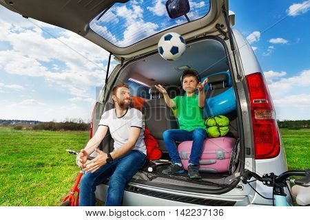 Active father playing ball with his son sitting in the car boot full of luggage