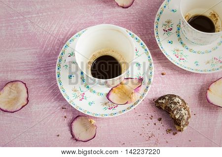 Two empty coffee cups and rose petals.