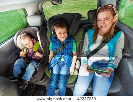 Two happy boys and mother are buckled with safety belt in a car, boys sitting in the safety car seat