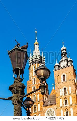 Fragment of Church of St. Mary in the main Market Square with lamppost and pigeons in the foreground. Basilica Mariacka. Krakow. Poland.