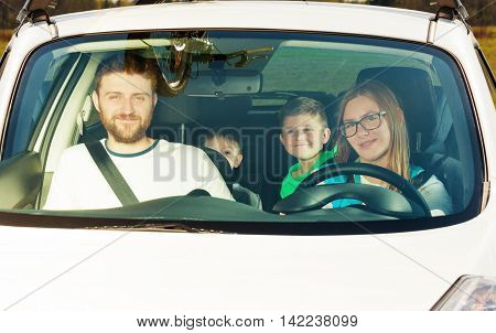 Happy female driver sitting in the car with her family, view through the windscreen